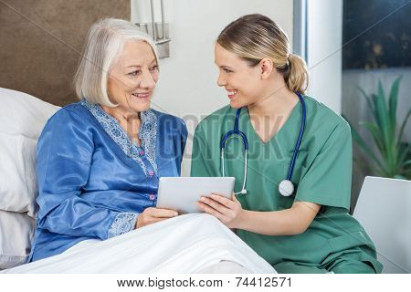 Happy female nurse and senior woman discussing while using tablet PC in bedroom at nursing home