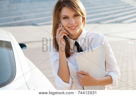 Business woman talking on her mobile phone. City business woman working.