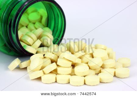 Folic acid spilling from green pill bottle