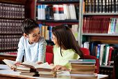 Happy little schoolgirls looking at each other while studying at table in library poster
