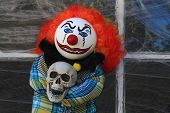 Typical Halloween Decorative Doll of Scary Creepy Character dolls Clown Killer in front of old house window cover by spider web. poster