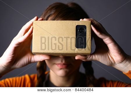 Color shot of a young woman looking through a cardboard a device with which one can experience virtual reality on a mobile phone. poster