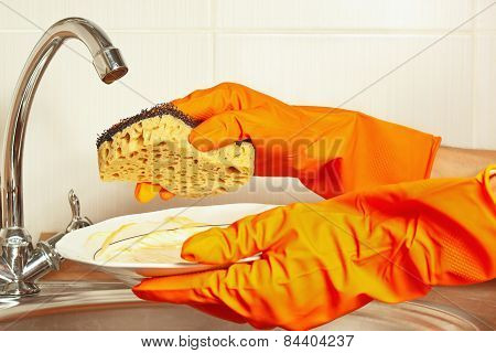 Hands in gloves with sponge and dirty saucer over the sink in kitchen