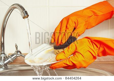 Hands in gloves with sponge wash dirty dishes under running water