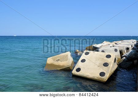 Coastline with concrete wave breaker in the shape of dice