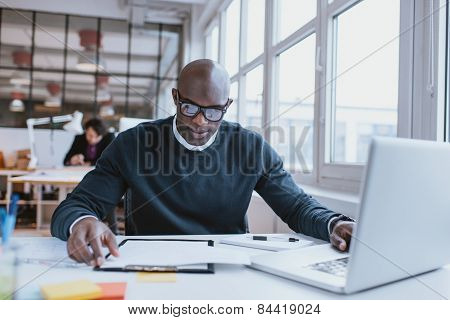 African Man Busy Working At Is Desk