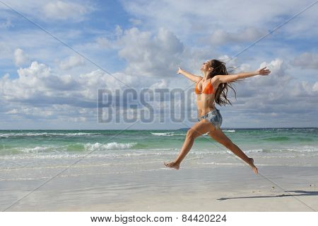 Happy Woman Jumping On The Beach On Holidays