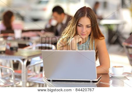 Woman Watching Media In A Laptop In A Coffee Shop