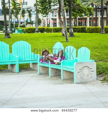 Homeless People Sleep On A Bench In South Beach