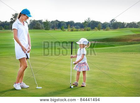 Mother And Daughter Practicing To Hit The Ball At The Course