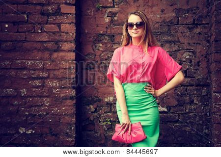 Beautiful Fashionable Woman at the Brick Wall