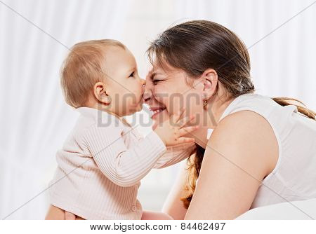 Woman and daughter playing in bed