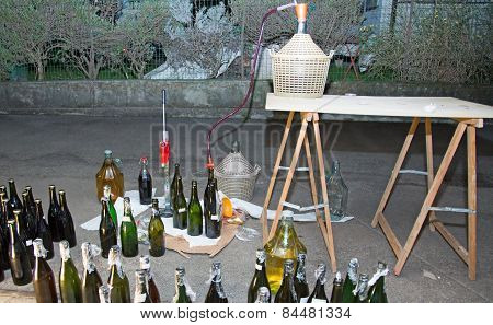 Wine Bottling In The Backyard With The Carboy And Glass Bottles