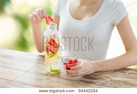 healthy eating, drinks, diet, detox and people concept - close up of woman with fruit water in glass bottle over green natural background