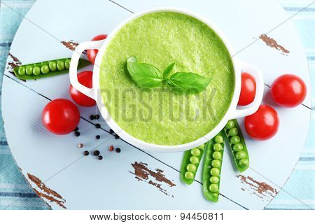 Tasty peas soup and vegetables on table close up poster