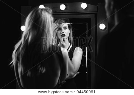 Image of an erotic woman applying lipstick poster