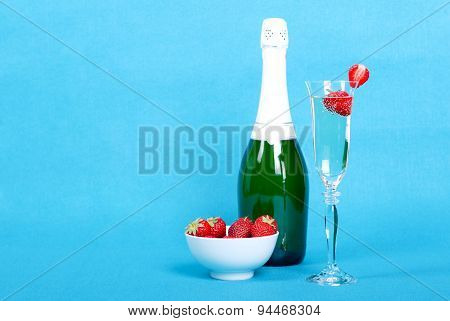 Glass With Champagne And Strawberries Slices Beside A Bottle Of Champagne And A Bowl Of Strawberries