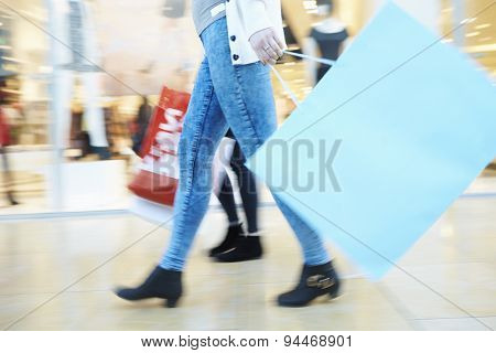 Close Up Of Shoppers Feet Carrying Bags In Shopping Mall