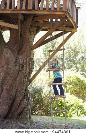 Young Girl Climbing Rope Ladder To Treehouse