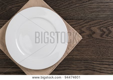 empty white plate on wood table with napkin