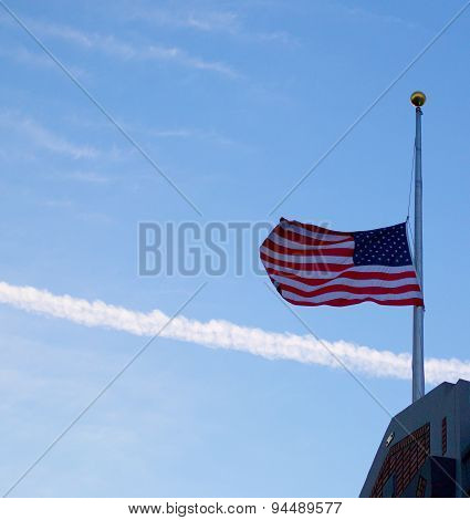 US Flag at half mast on top of a building