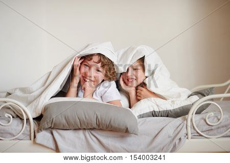 Two children brother and sister squirmy on the bed in the bedroom. They look out from under a blanket and laugh.