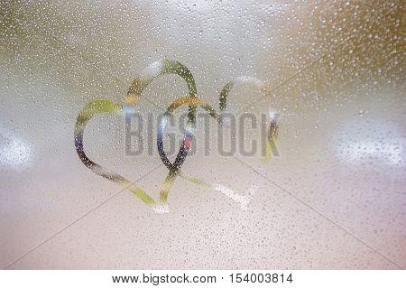 Two hearts drawn on a wet window glass. Rainy autumn