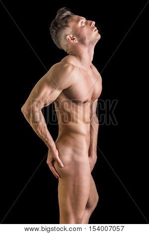 Portrait of totally naked handsome young man with languishing look covering crotch with hand
