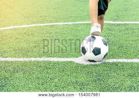 Feet of a boy wearing white sneakers stepping on a soccer ball in the middle of the football field.