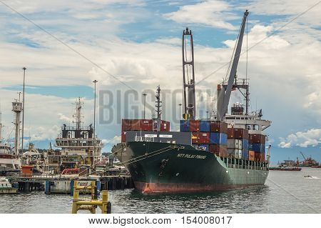 Labuan,Malaysia-Oct 27,2016:Container cargo freight ship with working crane loading bridge in shipyard at Labuan port.The port loads more then 99 percent of containerized goods through Labuan island.