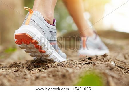 Freeze Action Closeup Of Young Woman Walking Or Running On Trail In Forest Or Park In Summer Nature