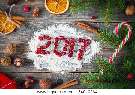 Happy New Year 2017! New Year, Christmas holiday card with cranberries, sweets, spices, Christmas tree and sweater on wooden background