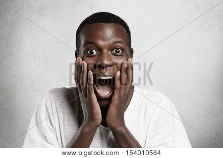 African Employee Or Customer With Shocked And Surprised Face, Looking And Screaming At Camera With B