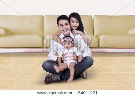 Photo of two young parents sitting on the floor with their daughter and smiling at the camera