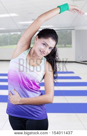 Beautiful Indian woman workout at gym while wearing sportswear and smiling at the camera