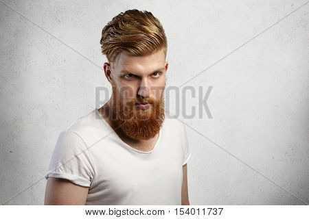 Headshot Of Self-assured Bearded Hipster With Stylish Haircut And Muscular Build Wearing T-shirt Wit