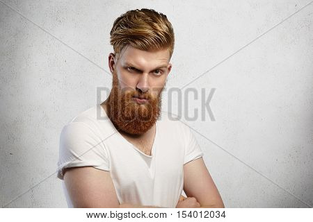 Studio Shot Of Attractive Bearded Young Caucasian Male Dressed In White T-shirt Standing On Blank Wa