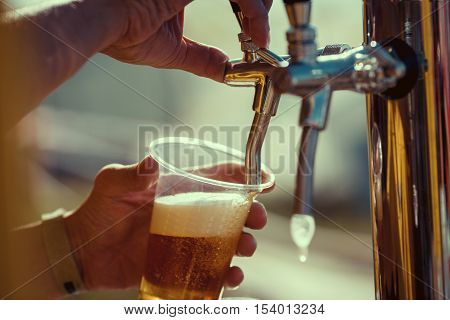 close-up of barman hand at beer tap pouring a draught lager beer poster