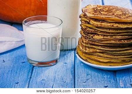 Stack of prepared pumpkin pancakes, glass and bottle of buttermilk
