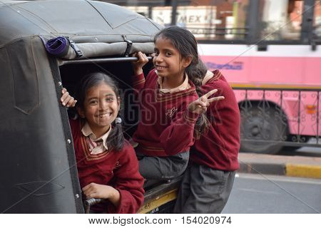JAIPUR, RAJASTHAN, INDIA - FEBRUARY 05, 2016 - Unidentified little indian girls smiling in uniform going to school in a truck