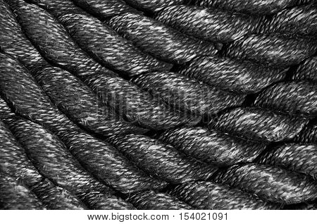Nautical background. Closeup of an old frayed boat rope. Monochromatic
