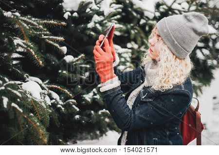 Young blond curly female tourist in warm clothes red gloves and bag making photo of spruce on smartphone