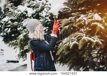 Young blond curly female tourist in warm clothes red gloves and bag is making photo of spruce or selfie on a smartphone