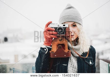 Young blond curly female in warm clothes with retro film camera shooting a photo on the background of winter city snow
