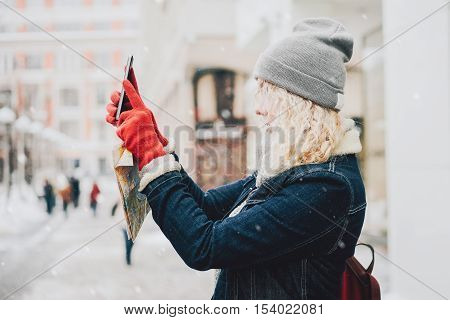 Young blond curly female tourist in warm clothes and red gloves with London map making photo or selfie on smartphone winter city blurred winter background