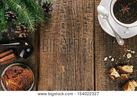 Cup of spiced tea and raisin cake on old brown wood with christmas decorations