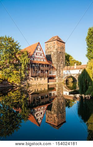 Hangman's Tower (Henkerturm) and traditional medieval half-timbered (fachwerk) house over the river Pegnitz in Nuremberg Germany