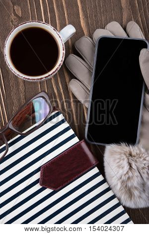 Cup of coffee gloves phone glasses Notepad in blue stripes