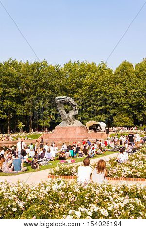 Warsaw Poland - September 11 2016: People enjoying open-air piano concert near Frederic Chopin monument in Royal Lazienki park (Royal Baths park) Warsaw.
