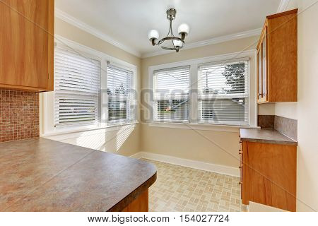 Beige Empty Dining Area With Cabinets And Linoleum